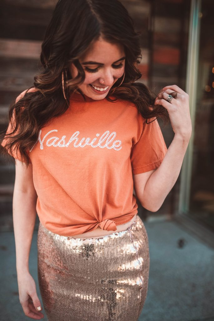 How to Style a Sequin Skirt | Greta Hollar | Graphic Tees by popular Nashville tall fashion blogger, Greta Hollar: image of Greta Hollar wearing a Nashville graphic tee with a gold sequin skirt.