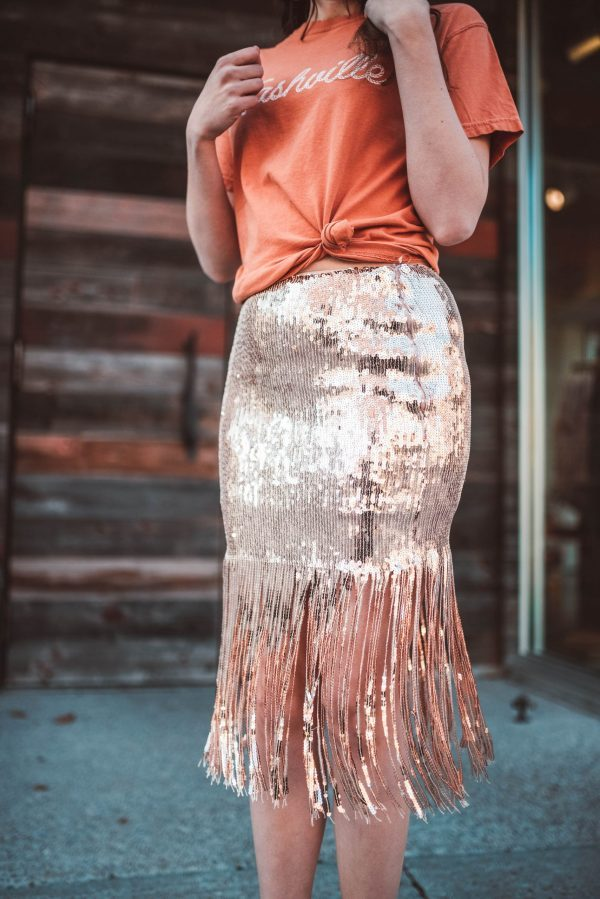 How to Style a Sequin Skirt | Greta Hollar | How to Style a Sequin Skirt by popular Nashville fashion blogger, Greta Hollar: image of a woman outside wearing a Vici WELCOME TO NASHVILLE COTTON TEE, Vici ON THE DANCE FLOOR SEQUIN TASSEL SKIRT, and Zappos Seychelles Black Tie.