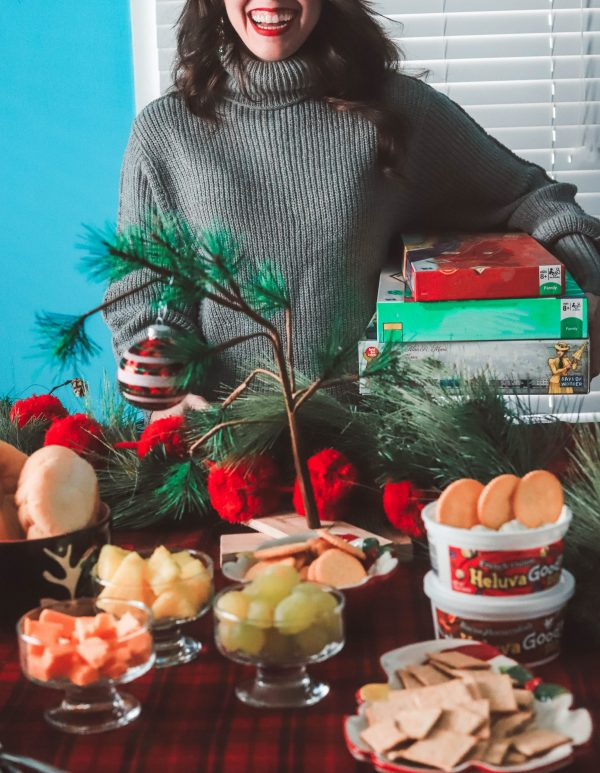 Holiday Game Night Essentials by popular life and style blogger, Greta Hollar: image of a woman holding a stack of board games and standing at a table set with various food items and Heluva Good dips.