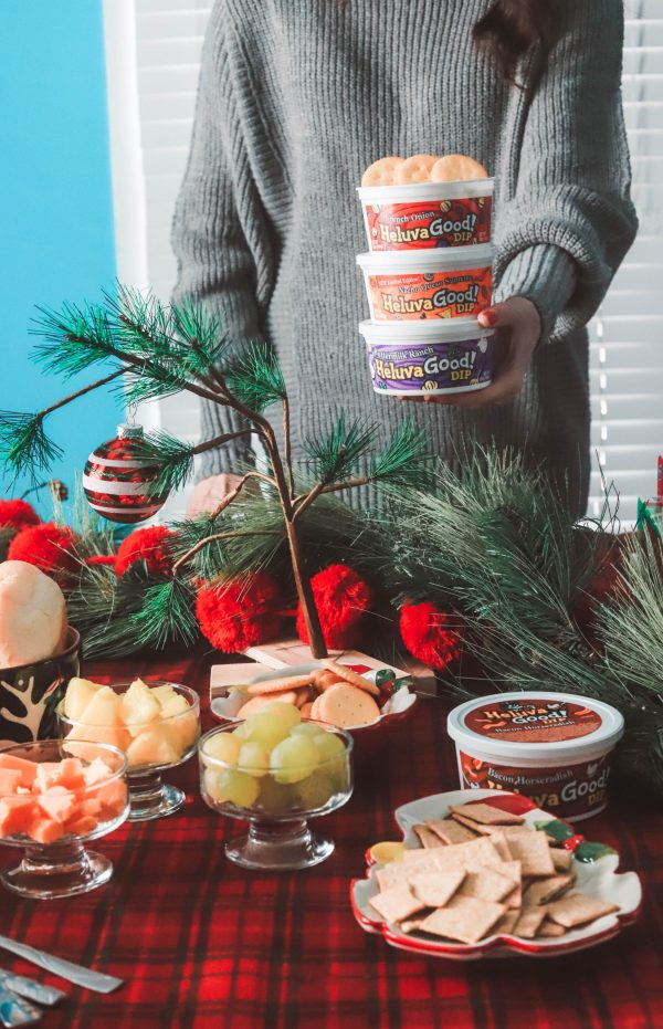 Holiday Game Night Essentials | Greta Hollar | Holiday Game Night Essentials by popular life and style blogger, Greta Hollar: image of a woman standing next to a table set with various finger food items and holding a stack of Heluva Good! dips.