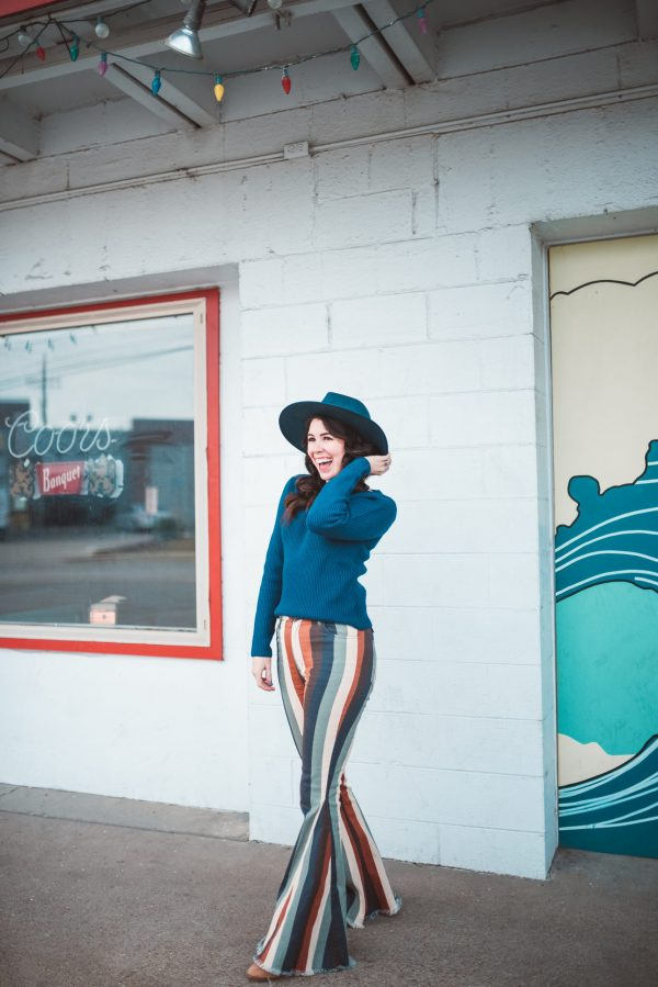 10 of My Current Favorites from Show Me Your Mumu | Greta Hollar | Show Me Your Mumu Pieces by popular Nashville tall fashion blogger, Greta Hollar: image of a woman wearing Show Me Your Mumu Berkeley Zip Up Bells, Show Me Your Mumu Lack of Color Rose Rancher Hat, and a blue ribbed long sleeve shirt.