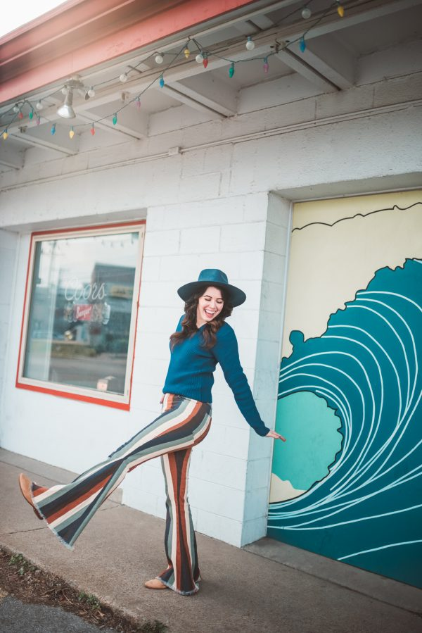 Rainy Day Activities in Nashville, TN | Greta Hollar  | Rainy Day Activities in Nashville, TN by popular Nashville blogger, Greta Hollar: image of a woman wearing striped flare jeans, a blue top, and a blue hat.