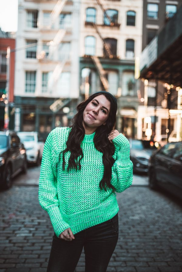 H&M Spring Collection: 3 Must Haves | Greta Hollar | Best Blogging Apps by popular Nashville blogger, Greta Hollar: image of a woman standing outside on a cobblestone street and wearing a green H&M sweater.