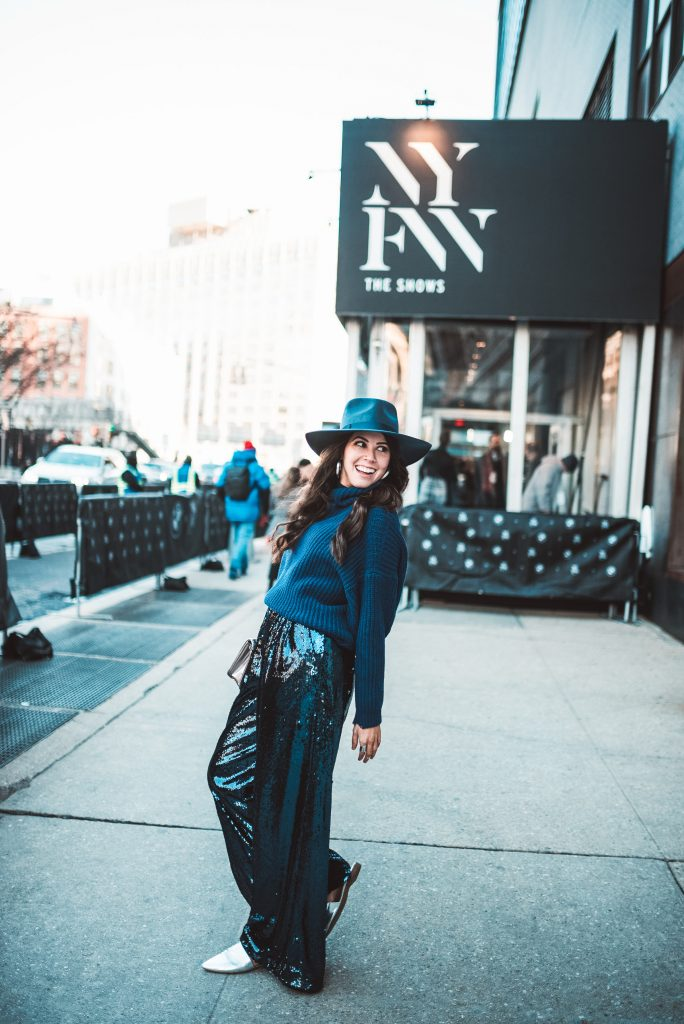 How to Wear Sequins in the Winter | Greta Hollar | Spring 2021 Fashion Trends by popular Nashville tall fashion blogger, Greta Hollar: image of Greta Hollar wearing blue sequin pants, blue knit sweater and a blue felt hat.
