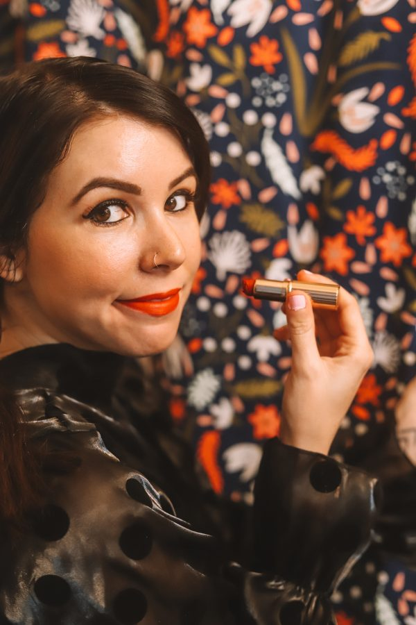 Top 4 Charlotte Tilbury Lipsticks for Spring | Greta Hollar | Charlotte Tilbury Lipsticks by popular Nashville beauty blogger, Greta Hollar: image of Greta Hollar holding a tube of Charlotte Tilbury Red Carpet Red lipstick.