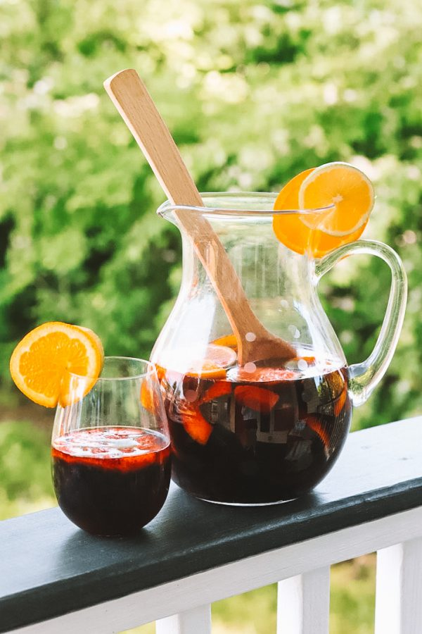 Summer Cocktail Ideas: a Refreshing Strawberry Sangria Recipe | Greta Hollar | Strawberry Sangria Recipe by popular Nashville lifestyle blogger, Greta Hollar: image of a glass drink pitcher and stemless wine glass filled with strawberry sangria.