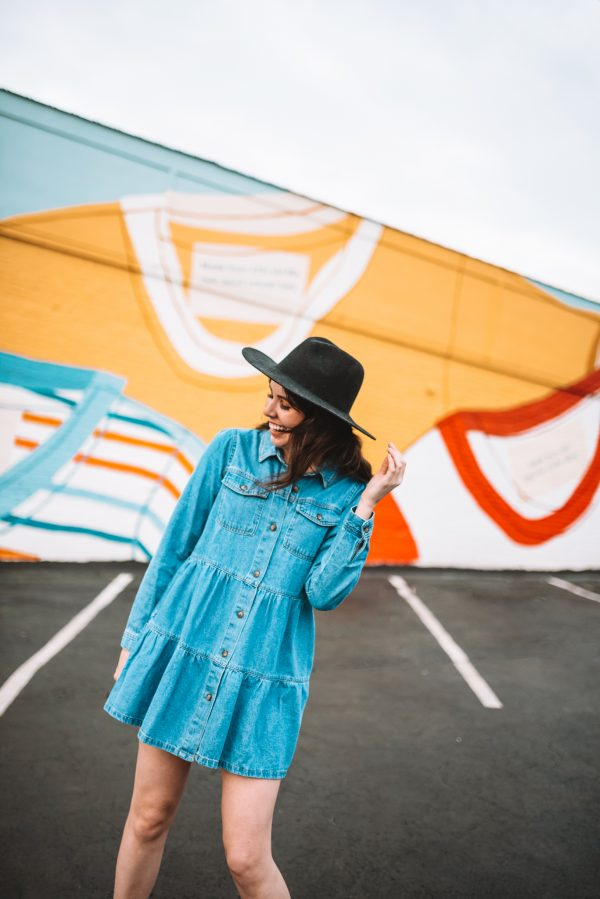 5 Things to Look Forward to Doing Once the Pandemic is Over | Greta Hollar | Things to Look Forward To by popular Nashville lifestyle blogger, Greta Hollar: image of a woman wearing a denim dress and black fedora hat and standing in front of a wall mural.