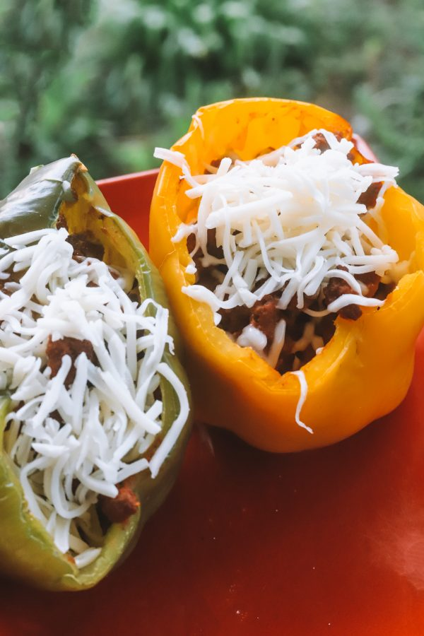 Easy Stuffed Bell Pepper Recipe with Ground Beef | Greta Hollar | Stuffed Bell Peppers With Ground Beef by popular Nashville lifestyle blogger, Greta Hollar: image of two stuffed bell peppers with ground beef on a red plate.