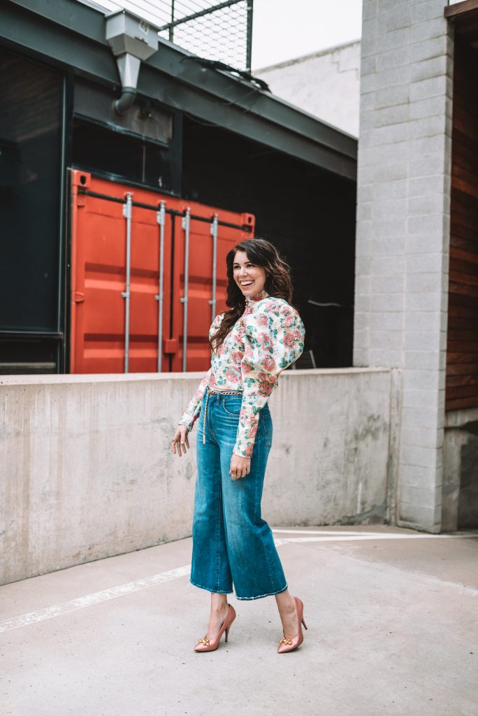 5 Cute Valentine's Day Looks that Aren't Dresses | Greta Hollar |Valentine's Day Looks by popular Nashville tall fashion blogger, Greta Hollar: image of Greta Hollar wearing a  puff sleeve floral print shirt and flare leg crop jeans.