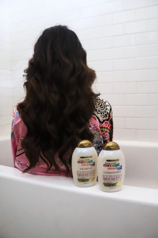 My Head-to-Toe Self-Care Routine: 4 Ways to Practice Self-Care at Home | Greta Hollar | Self Care at Home by popular Nashville lifestyle blogger, Greta Hollar: image of a woman sitting in a tub next to a bottle OGX Coconut Miracle Oil conditioner and OGX Coconut Miracle Oil shampoo.