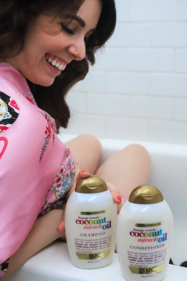 Self Care at Home by popular Nashville lifestyle blogger, Greta Hollar: image of a woman sitting in a tub next to a bottle OGX Coconut Miracle Oil conditioner and OGX Coconut Miracle Oil shampoo.