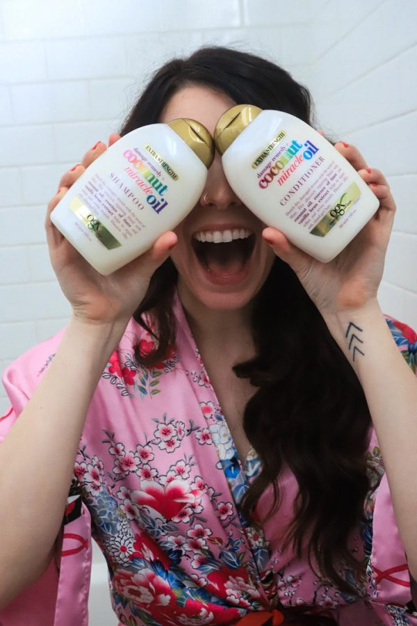 Self Care at Home by popular Nashville lifestyle blogger, Greta Hollar: image of a woman wearing a pink robe and holding a bottle OGX Coconut Miracle Oil conditioner and OGX Coconut Miracle Oil shampoo.