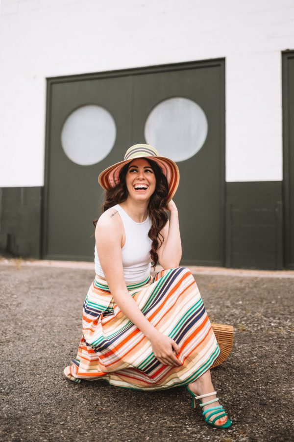 Orange Clothing by popular Nashville tall fashion blogger, Greta Hollar: image of Greta Hollar wearing a multi color stripe skirt, white tank and strip straw hat.