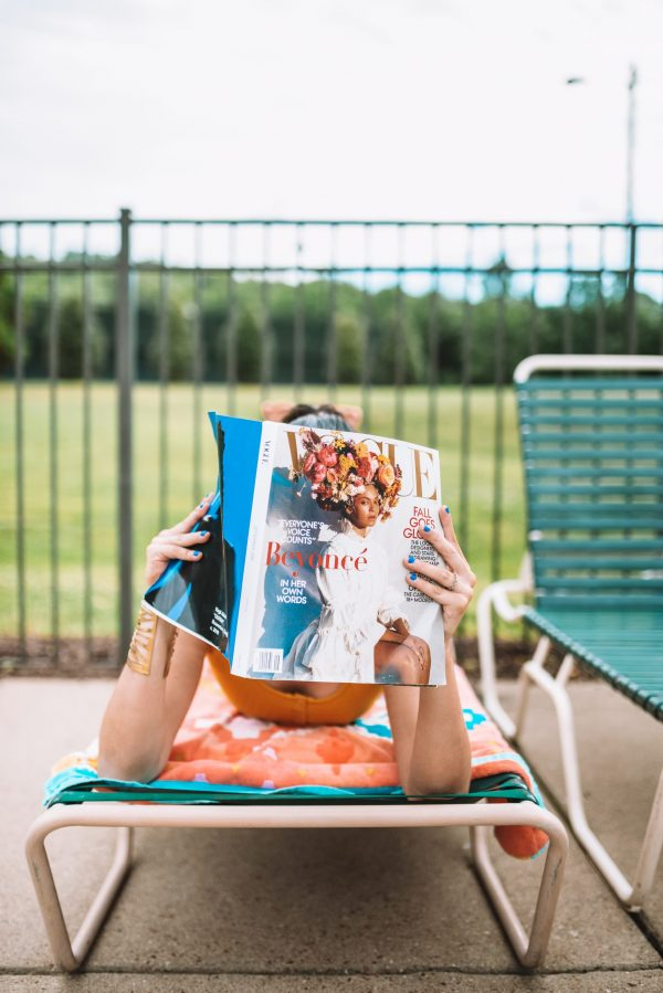 Everything You Need for a Day at the Pool: 5 Essential Items | Greta Hollar | Pool Essentials by popular Nashville lifestyle blogger, Greta Hollar: image of Greta Hollar wearing a yellow two piece swimsuit and white frame sunglasses with yellow lenses while laying in a lounge chair by the pool with a magazine in her hands.