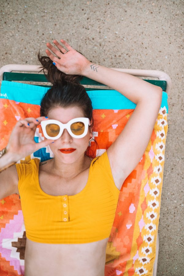 Everything You Need for a Day at the Pool: 5 Essential Items | Greta Hollar | Pool Essentials by popular Nashville lifestyle blogger, Greta Hollar: image of Greta Hollar wearing a yellow two piece swimsuit and white frame sunglasses with yellow lenses while laying in a lounge chair by the pool.