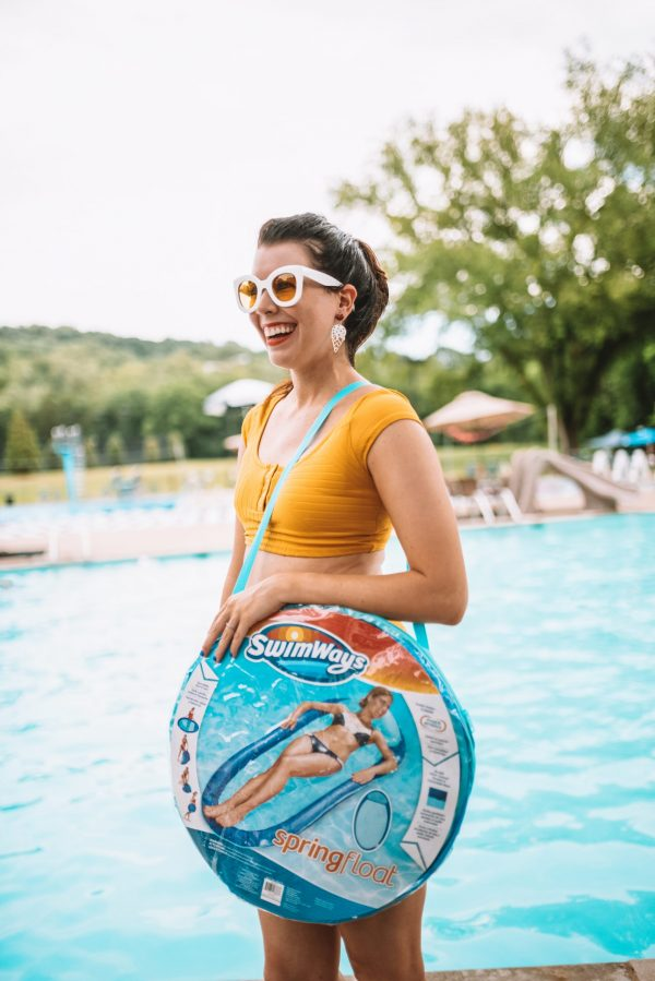 Everything You Need for a Day at the Pool: 5 Essential Items | Greta Hollar | Pool Essentials by popular Nashville lifestyle blogger, Greta Hollar: image of Greta Hollar wearing a yellow two piece swimsuit and white frame sunglasses with yellow lenses while standing next to the pool and holding a Walmart SwimWays Spring Float Papasan.