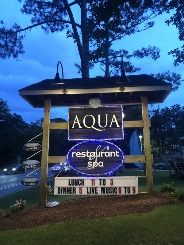 COVID Travel: The Best Things to Do Outer Banks, NC When Social Distancing | Greta Hollar |  Outer Banks NC by popular Nashville travel blogger, Greta Hollar: image of Aqua restaurant and spa sign.