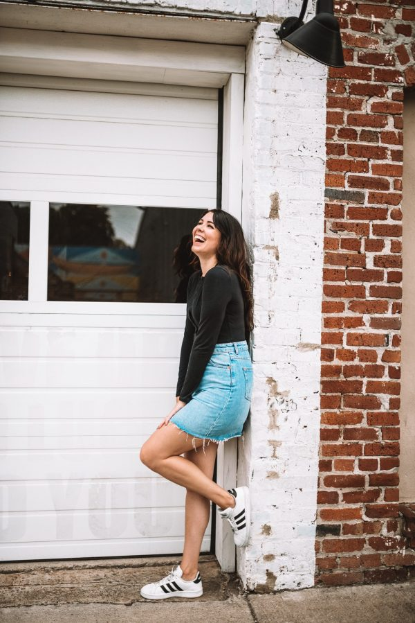 Hello September and Fall Fashion!   Greta Hollar   Fall Clothing by popular Nashville tall fashion blogger, Greta Hollar: image of Greta Hollar leaning against a white brick wall and wearing a long sleeve black body suit, denim skirt, and pair of white Adidas sneakers.