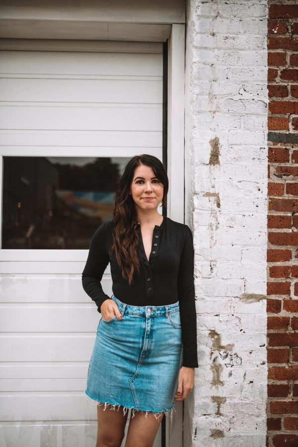 Hello September and Fall Fashion! | Greta Hollar | Fall Clothing by popular Nashville tall fashion blogger, Greta Hollar: image of Greta Hollar leaning against a white brick wall and wearing a long sleeve black body suit and denim skirt.