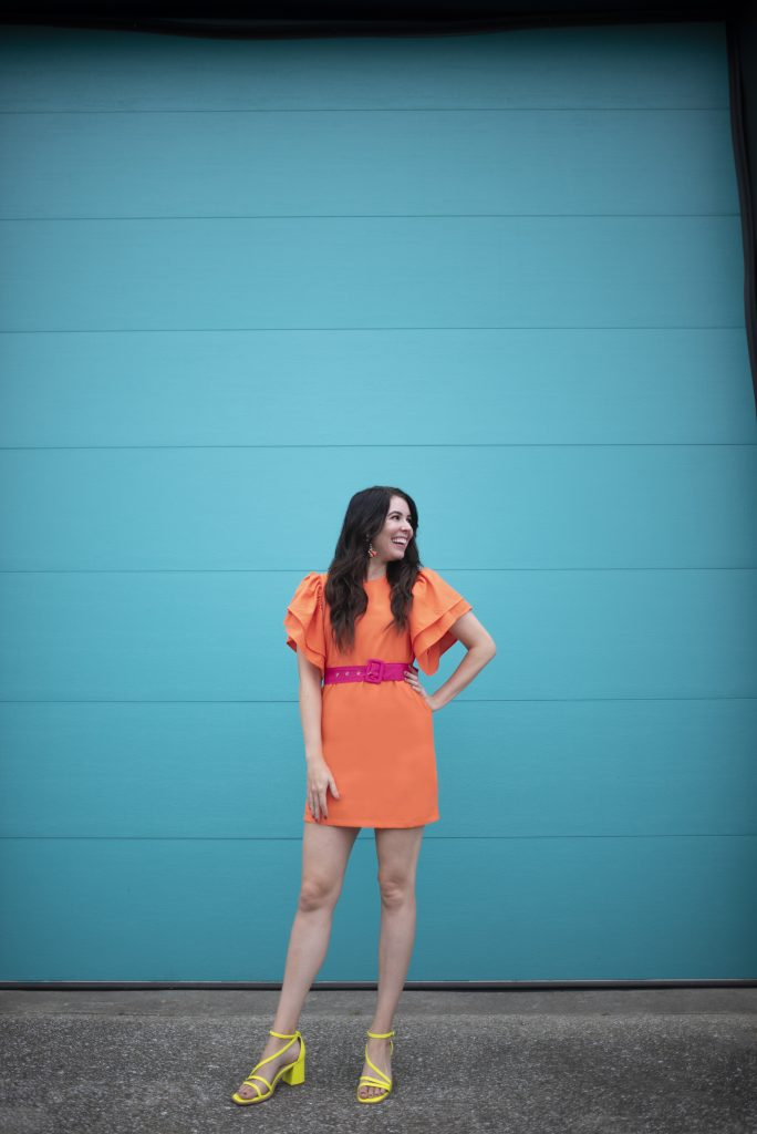 Orange Clothing: Top 5 Pieces to Wear this Fall | Greta Hollar | Orange Clothes by popular Nashville tall fashion blogger, Greta Hollar: image of Greta Hollar standing in front of a blue wall and wearing a orange ruffle sleeve dress with a pink belt and yellow block heel sandals.