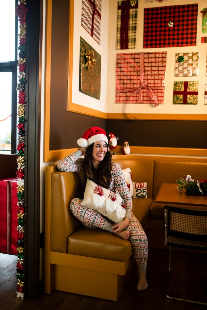 A Cute and Festive Christmas Morning Outfit to Open your Gifts | Greta Hollar | Christmas Outfit by popular Nashville tall fashion blogger, Greta Hollar: image of Greta Hollar sitting in a restaurant booth and wearing a Santa hat and nordic pajama set.