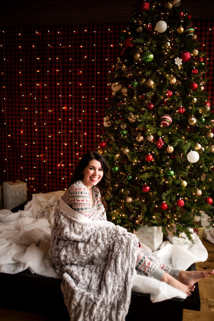 A Cute and Festive Christmas Morning Outfit to Open your Gifts | Greta Hollar | Christmas Outfit by popular Nashville tall fashion blogger, Greta Hollar: image of Greta Hollar sitting next to a Christmas tree and wearing a Santa hat and nordic pajama set.