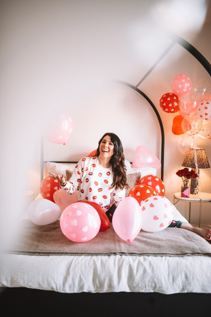 Loungewear Sets by popular Nashville tall fashion blogger, Greta Hollar: image of a woman sitting on a bed surrounded by heart balloons and wearing a lip and heart print loungewear set.