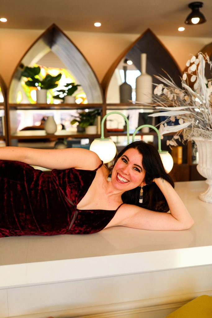 5 Things to Wear Under A Plunging V | Greta Hollar |Plunging V Neck by popular Nashville fashion blogger, Greta Hollar: image of Greta Hollar laying on a white counter top and wearing a deep red velvet plunging v neck dress.