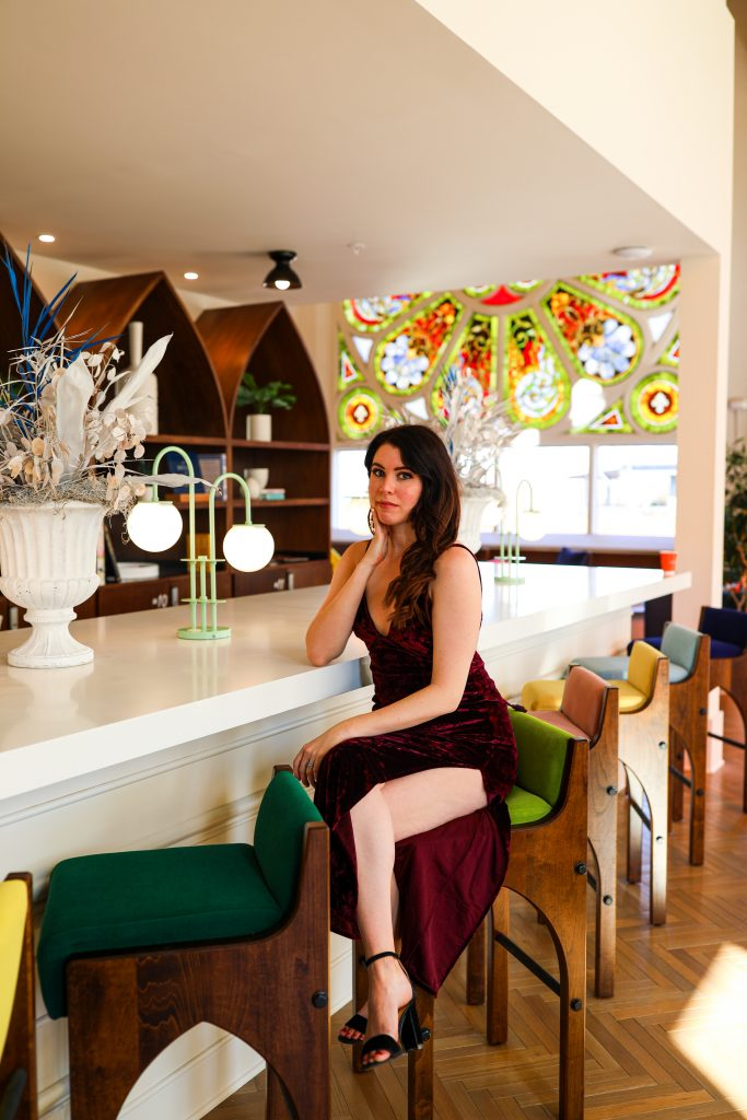 5 Things to Wear Under A Plunging V | Greta Hollar |Plunging V Neck by popular Nashville fashion blogger, Greta Hollar: image of Greta Hollar sitting at a white counter top and wearing a deep red velvet plunging v neck dress.