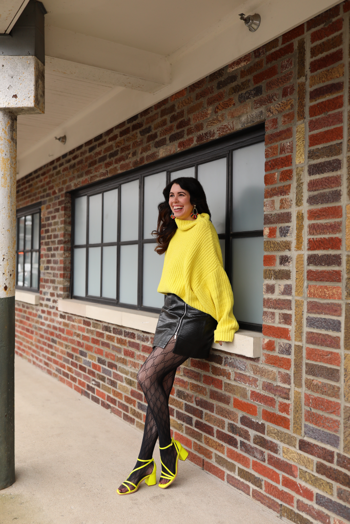 Top 4 Spring 2021 Fashion Trends to Wear | Greta Hollar |Spring 2021 Fashion Trends by popular Nashville tall fashion blogger, Greta Hollar: image of Greta Hollar wearing a bright yellow knit sweater, black vegan leather skirt, black tights, and yellow block heel strapy sandals.