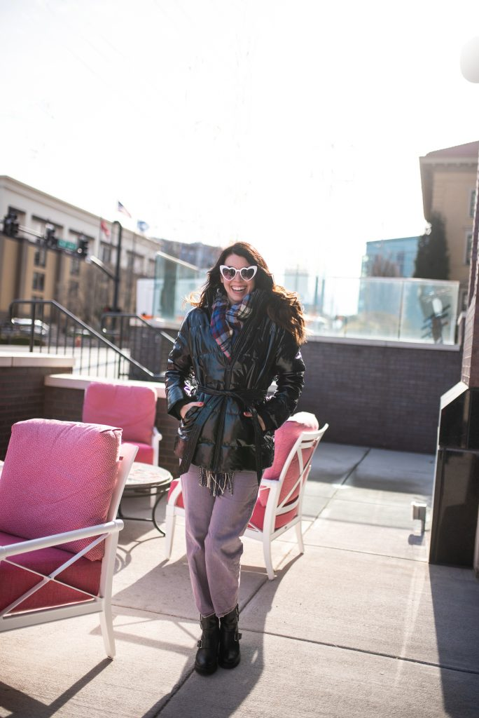 Style Guide:What to Wear on a Cold Valentine's Day | Greta Hollar |What to Wear on Valentine's Day by popular Nashville tall fashion blogger, Greta Hollar: image of Greta Hollar wearing white heart frame sunglasses, plaid scarf, black tie waist puffer jacket, purple pants and black ankle boots.