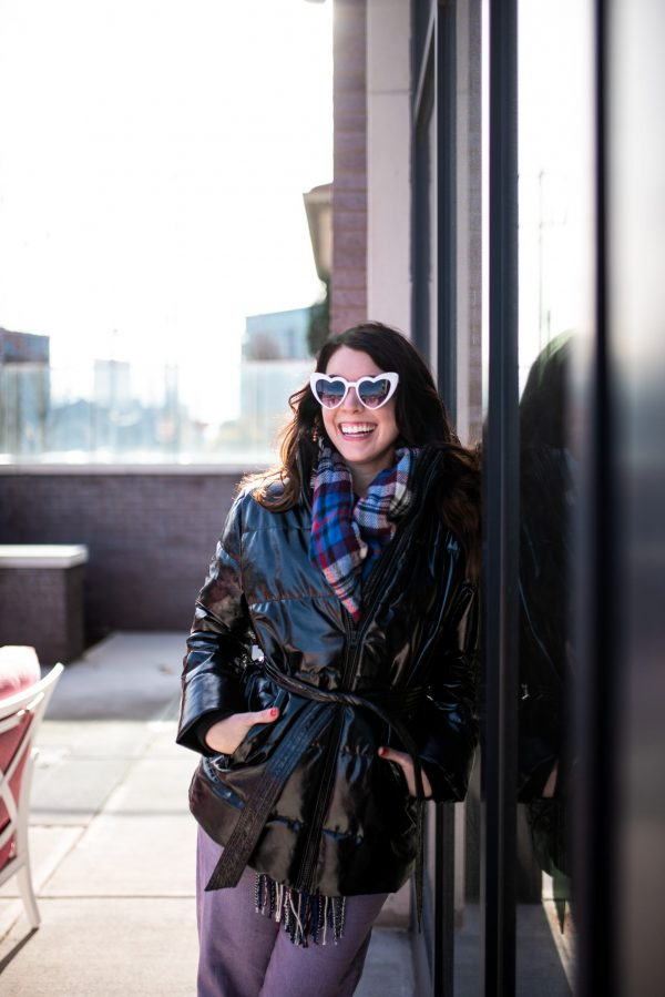 Style Guide:What to Wear on a Cold Valentine's Day | Greta Hollar | What to Wear on Valentine's Day by popular Nashville tall fashion blogger, Greta Hollar: image of Greta Hollar wearing white heart frame sunglasses, plaid scarf, black tie waist puffer jacket, purple pants and black ankle boots.