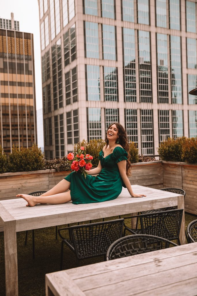 4 Dresses That are Perfect for Spring | Greta Hollar |Spring Dresses by popular Nashville tall fashion blogger, Greta Hollar: image of Greta Hollar wearing a green satin dress and holding a bouquet of pink flowers while sitting on a table outside.