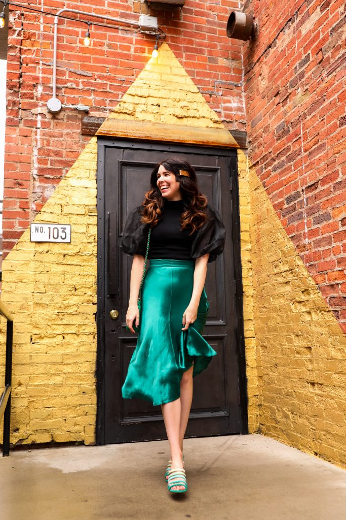 St. Patrick's Day Fashion 3 Outfit Ideas for Tall Women | Greta Hollar | St. Patrick's Day Fashion by popular Nashville tall fashion blogger, Greta Hollar: image of Greta Hollar wearing a green satin skirt, black puff sleeve top, and green strappy sandals.