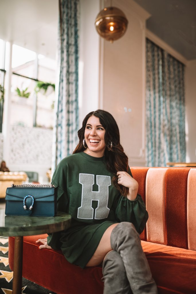 St. Patrick's Day Fashion 3 Outfit Ideas for Tall Women | Greta Hollar |St. Patrick's Day Fashion by popular Nashville tall fashion blogger, Greta Hollar: image of Greta Hollar wearing a green sweatshirt dress and grey suede over the knee boots.