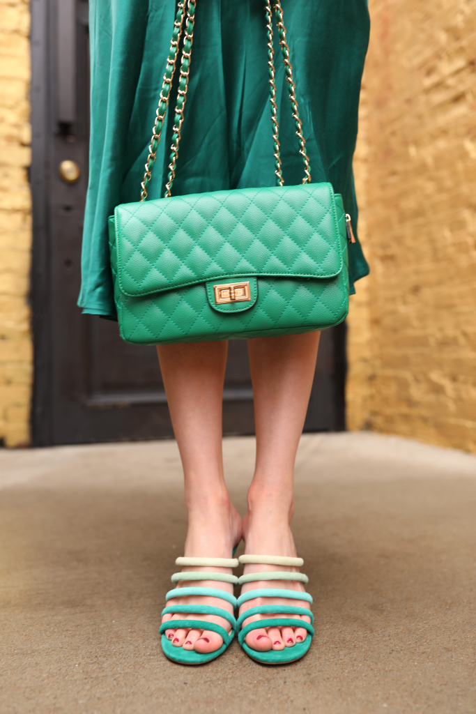 St. Patrick's Day Fashion 3 Outfit Ideas for Tall Women | Greta Hollar |Greta Hollar | St. Patrick's Day Fashion by popular Nashville tall fashion blogger, Greta Hollar: image of Greta Hollar wearing a green satin skirt, black puff sleeve top, and green strappy sandals.