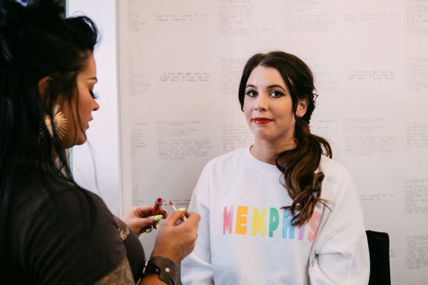 The Ultimate Memphis Trip with your Girlfriends | Greta Hollar |Memphis Trip by popular Nashville travel blogger, Greta Hollar: image of Greta Hollar wearing a Memphis sweatshirt while getting her makeup applied by another woman.