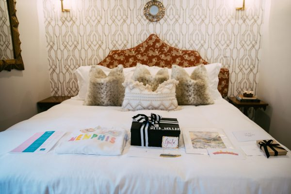 Memphis Trip by popular Nashville travel blogger, Greta Hollar: image of a hotel bed covered with clothing, art prints, and jewelry.