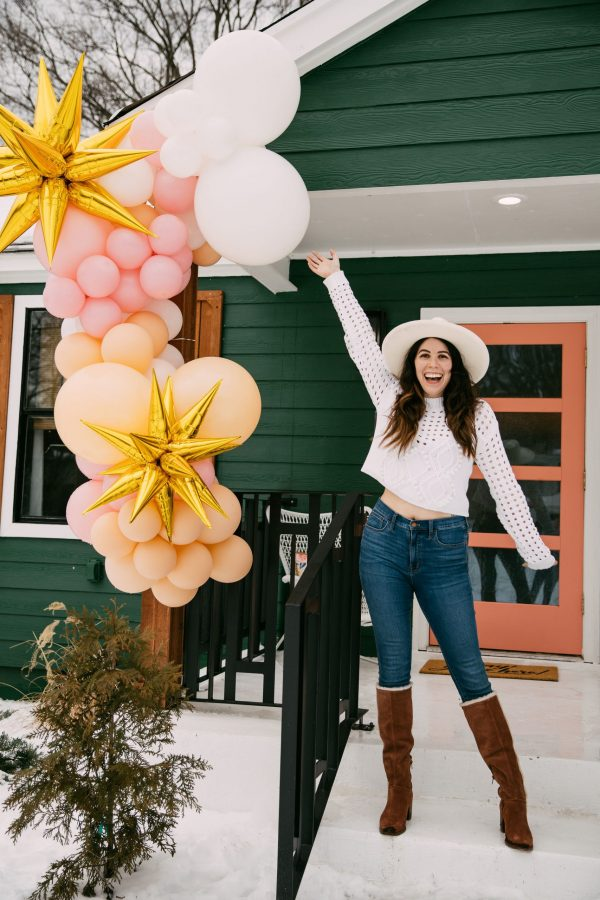 Memphis Trip by popular Nashville travel blogger, Greta Hollar: image of Greta Hollar wearing a white sweater, jeans, white hat, and knee high brown suede boots while standing next to a balloon garland.