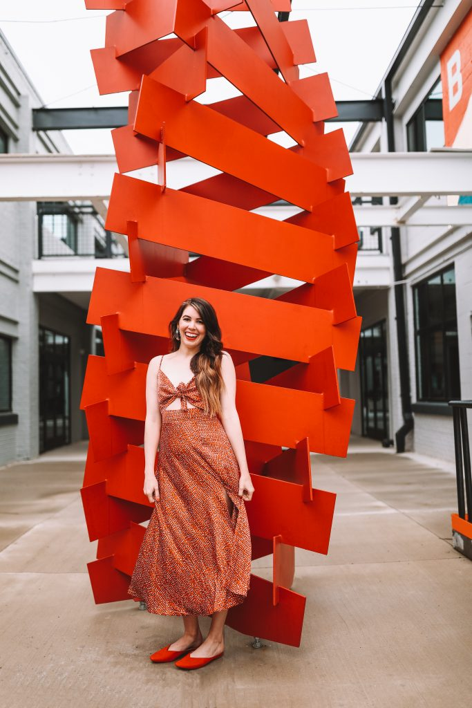 Spring Style: 4 Memorial Day Outfit Ideas for the Tall Woman | Greta Hollar | Memorial Day Outfits by popular Nashville tall fashion blogger, Greta Hollar: image of Greta Hollar standing by a red modern art sculpture and wearing a red and white cutout tie front dress and red slide flats.