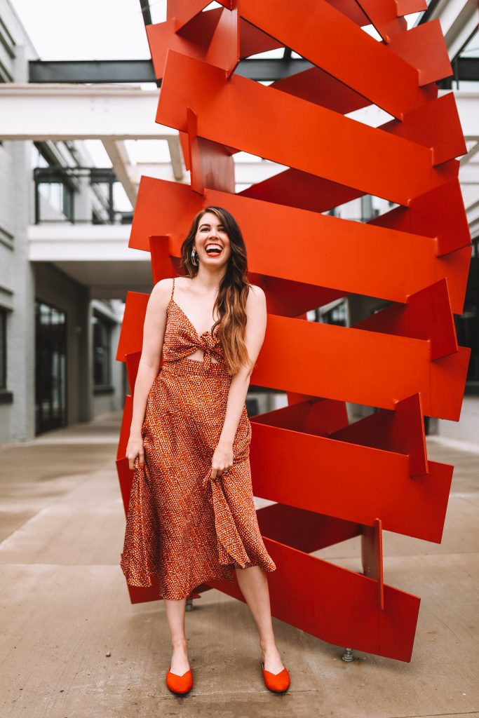 Spring Style: 4 Memorial Day Outfit Ideas for the Tall Woman | Greta Hollar |Memorial Day Outfits by popular Nashville tall fashion blogger, Greta Hollar: image of Greta Hollar standing by a red modern art sculpture and wearing a red and white cutout tie front dress and red slide flats.