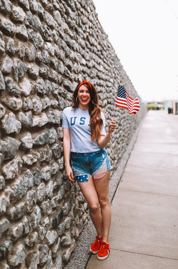 Spring Style: 4 Memorial Day Outfit Ideas for the Tall Woman | Greta Hollar |Memorial Day Outfits by popular Nashville tall fashion blogger, Greta Hollar: image of Greta Hollar wearing a grey USA t-shirt, denim cut off shorts with American Flag print pockets and red sneakers.