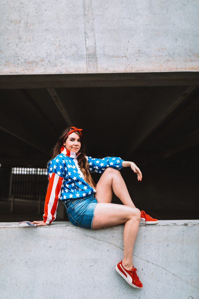 Spring Style: 4 Memorial Day Outfit Ideas for the Tall Woman | Greta Hollar |Memorial Day Outfits by popular Nashville tall fashion blogger, Greta Hollar: image of Greta Hollar wearing an american flag print wind breaker jacket, denim shorts, red sneakers, and red bandana hair tie.