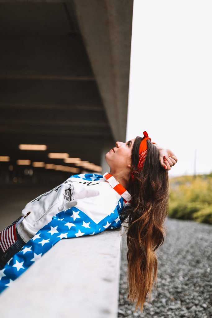 Spring Style: 4 Memorial Day Outfit Ideas for the Tall Woman | Greta Hollar |Memorial Day Outfits by popular Nashville tall fashion blogger, Greta Hollar: image of Greta Hollar wearing an american flag print wind breaker jacket, and red bandana hair tie.