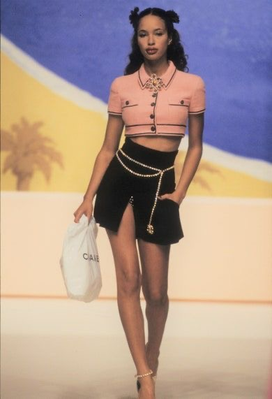 Timeless Fashion: How to Recreate 3 Classic 90s Looks Using your Favorite Modern Day Pieces | Greta Hollar |Classic 90s Looks by popular Nashville fashion blogger, Greta Hollar: image of a woman wearing a pink tweed crop top, black slit mini skirt, and gold chain belt.