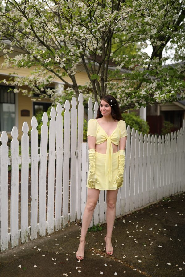 How to Recreate 3 Classic 90s Looks Using your Favorite Modern Day Pieces | Greta Hollar |Classic 90s Looks by popular Nashville fashion blogger, Greta Hollar: image of Greta Hollar standing by a white picket fence and wearing a yellow two piece top and skirt set with yellow arm length gloves, daisy hair clips and nude strap sandals.
