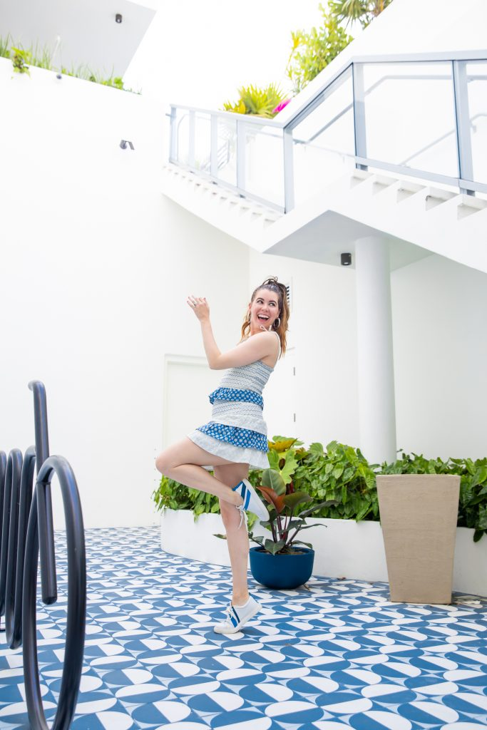 Hotel Review: The Moxy South Beach   Greta Hollar   The Moxy South Beach by popular Nashville travel blogger, Greta Hollar: image of Greta Hollar wearing a white and blue print dress, white sneakers with a blue stripe, and standing on a blue and white tile floor at the Moxy South Beach.