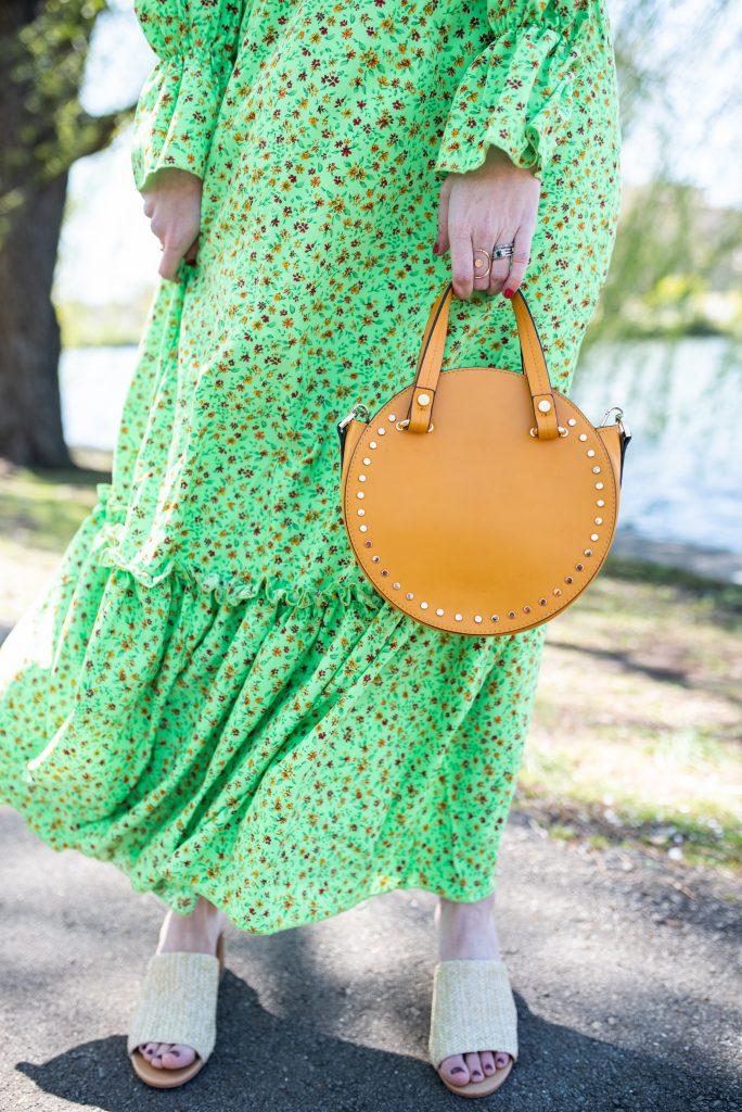 Top 7 Favorite Handbags for Summer | Greta Hollar | Summer Handbags by popular Nashville tall fashion blogger, Greta Hollar: image of Greta Hollar wearing a green floral print maxi dress and holding a tan circle handbag.