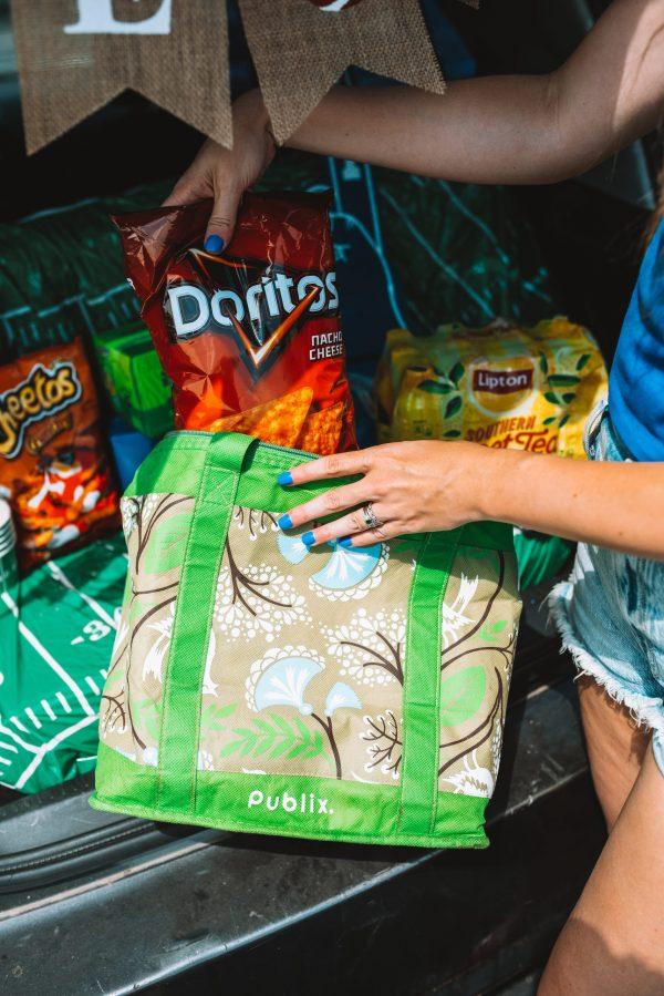 How to Tailgate by popular Nashville lifestyle blogger, Greta Hollar: image of Greta Hollar putting a bag of Doritos into a Publix reusable shopping bag.