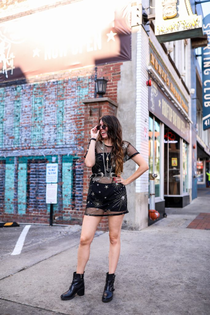 4 Outfit Ideas for Bonnaroo | Greta Hollar | Bonnaroo Outfits by popular Nashville tall fashion blogger, Greta Hollar: image of Greta Hollar wearing a black star print see-through dress with a silver layer necklace, black sunglasses, and black combat boots.